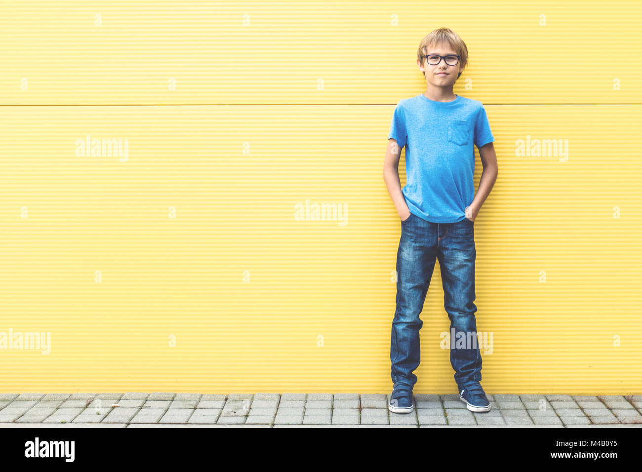 Boy with glasses standing near yellow wall outdoors - Stock Image