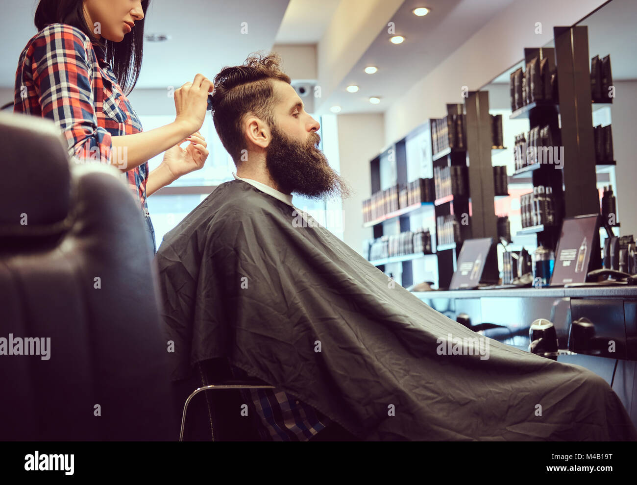 Handsome bearded man in the barbershop. - Stock Image