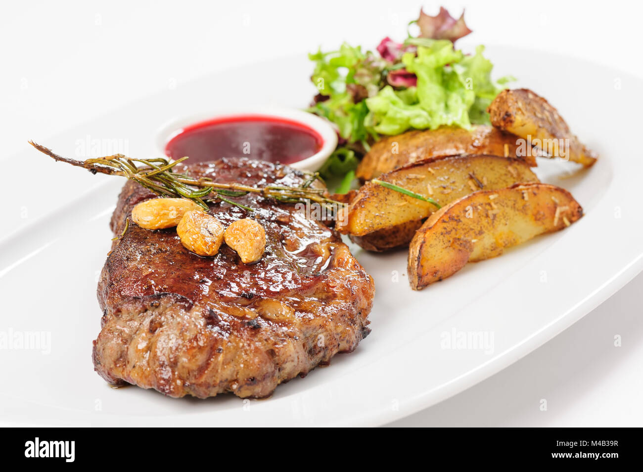 Thick juicy beef steak with potato and salad - Stock Image