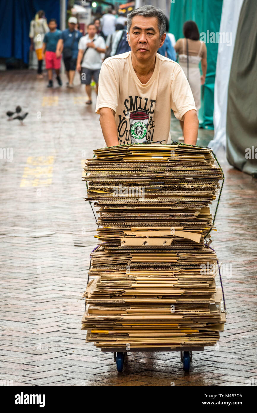 Older man collects cardboard packagings in Chinatown,Singapore - Stock Image