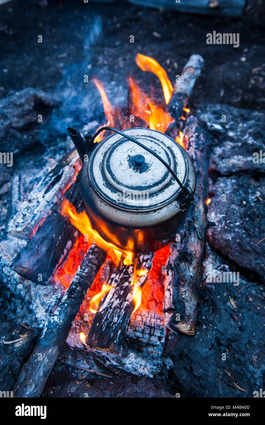 Boiling water pot over an open fire on a campsite on Tolbachik volcano,Kamchatka,Russia - Stock Image