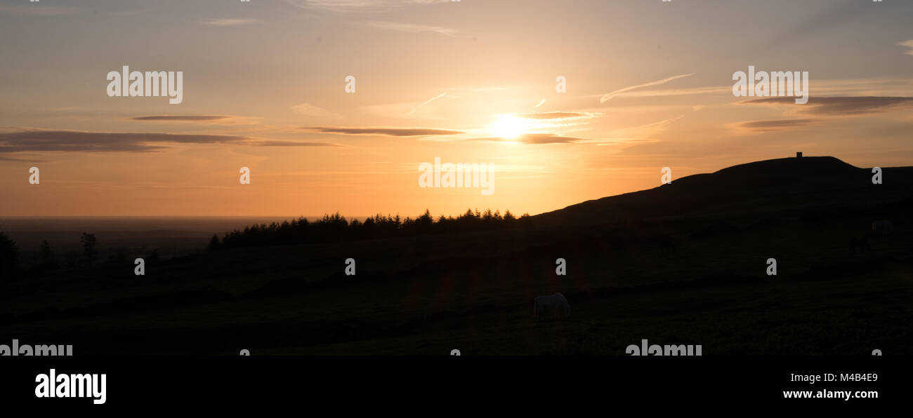 Late evening photograph from Winter Hill looking towards Rivington Pike silhouetted against the warm glow of the - Stock Image
