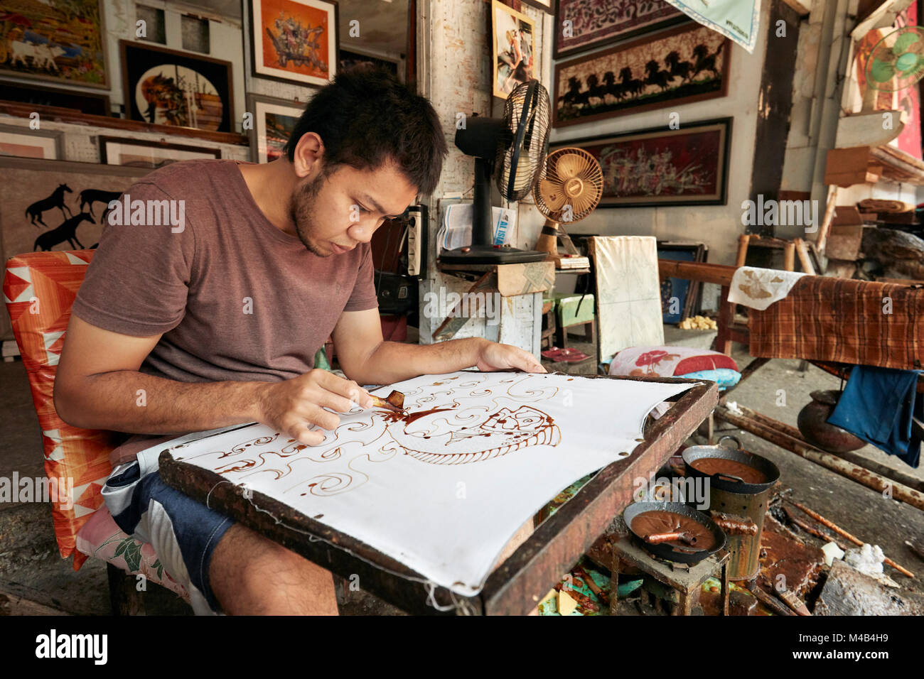 Artisan painting batik with a canting (spouted tool) in Batik Seno shop. Yogyakarta, Java, Indonesia. - Stock Image