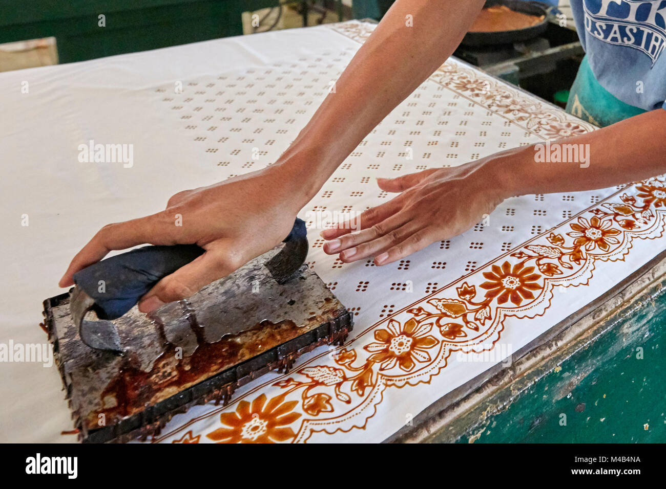 Batik maker printing the hot wax-resist dyeing on a cloth with a Cap (copper stamp). Batik Winotosastro shop, Yogyakarta, - Stock Image