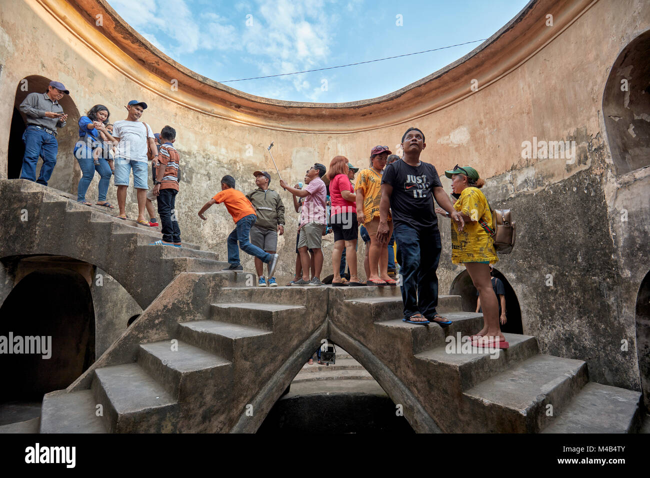 People in Gumuling Well (Sumur Gumuling), one-storeyed circular structure, once used as a mosque. Taman Sari Water Stock Photo