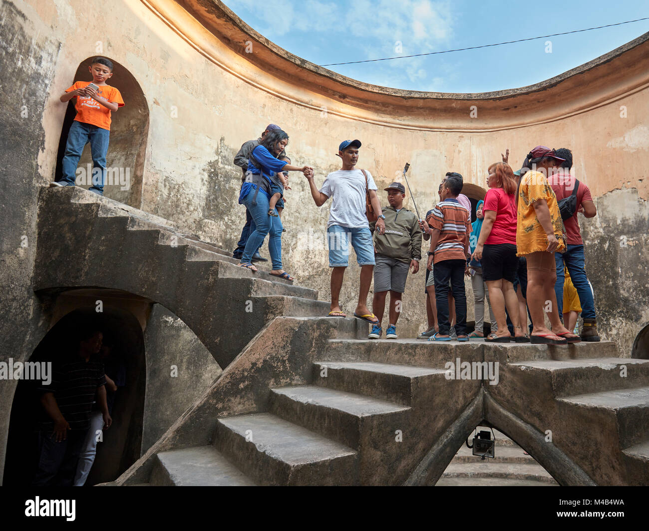 People in Gumuling Well (Sumur Gumuling), one-storeyed circular structure, once used as a mosque. Taman Sari Water - Stock Image