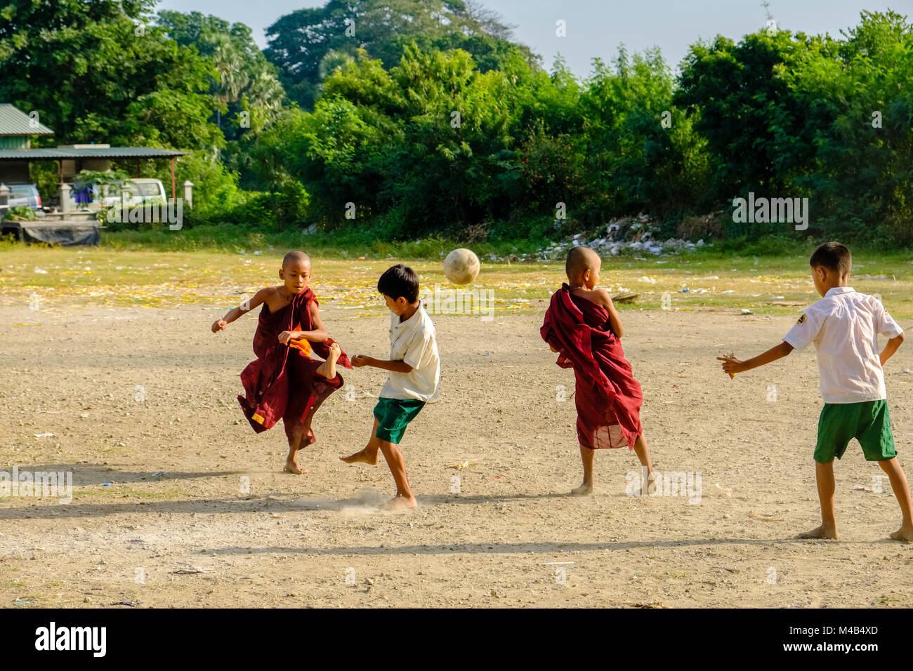 Young monks are playing football with the local boys Stock Photo