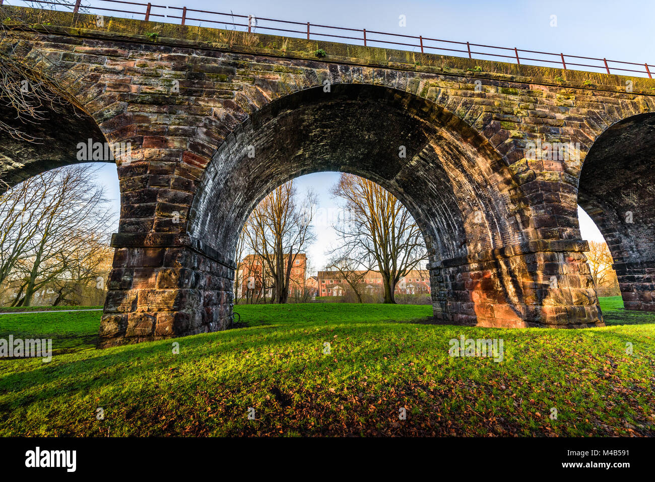 Old Victorian railway viaduct arches framing trees and new houses in Northwich, Cheshire, UK. - Stock Image