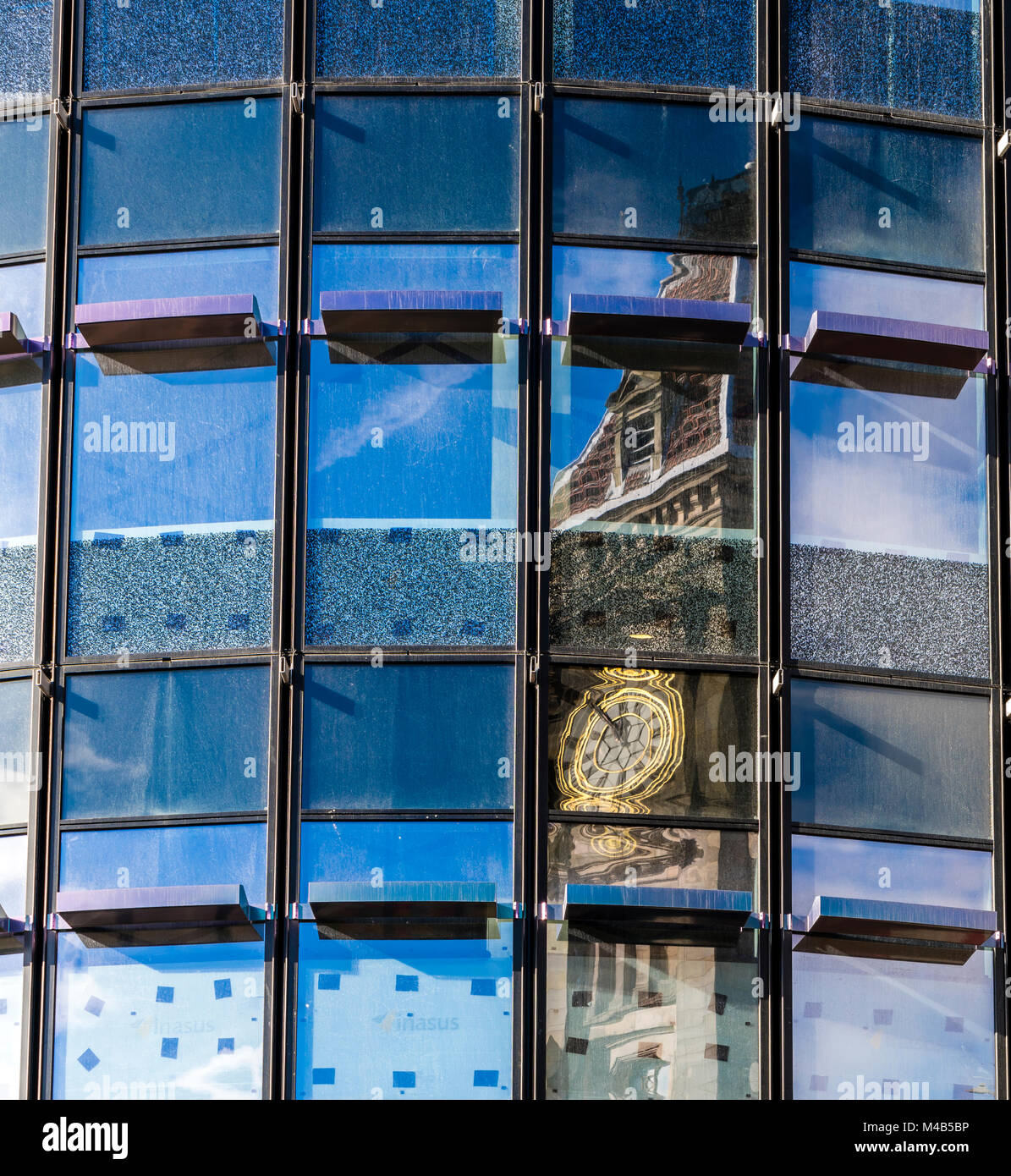 Reflection of a clock tower in a new building in Birmingham, UK - Stock Image