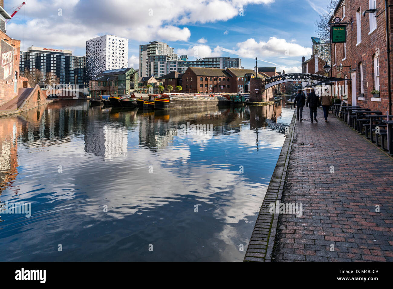 Views of the canal with reflections of people and buildings in Brindley Place Birmingham, UK - Stock Image
