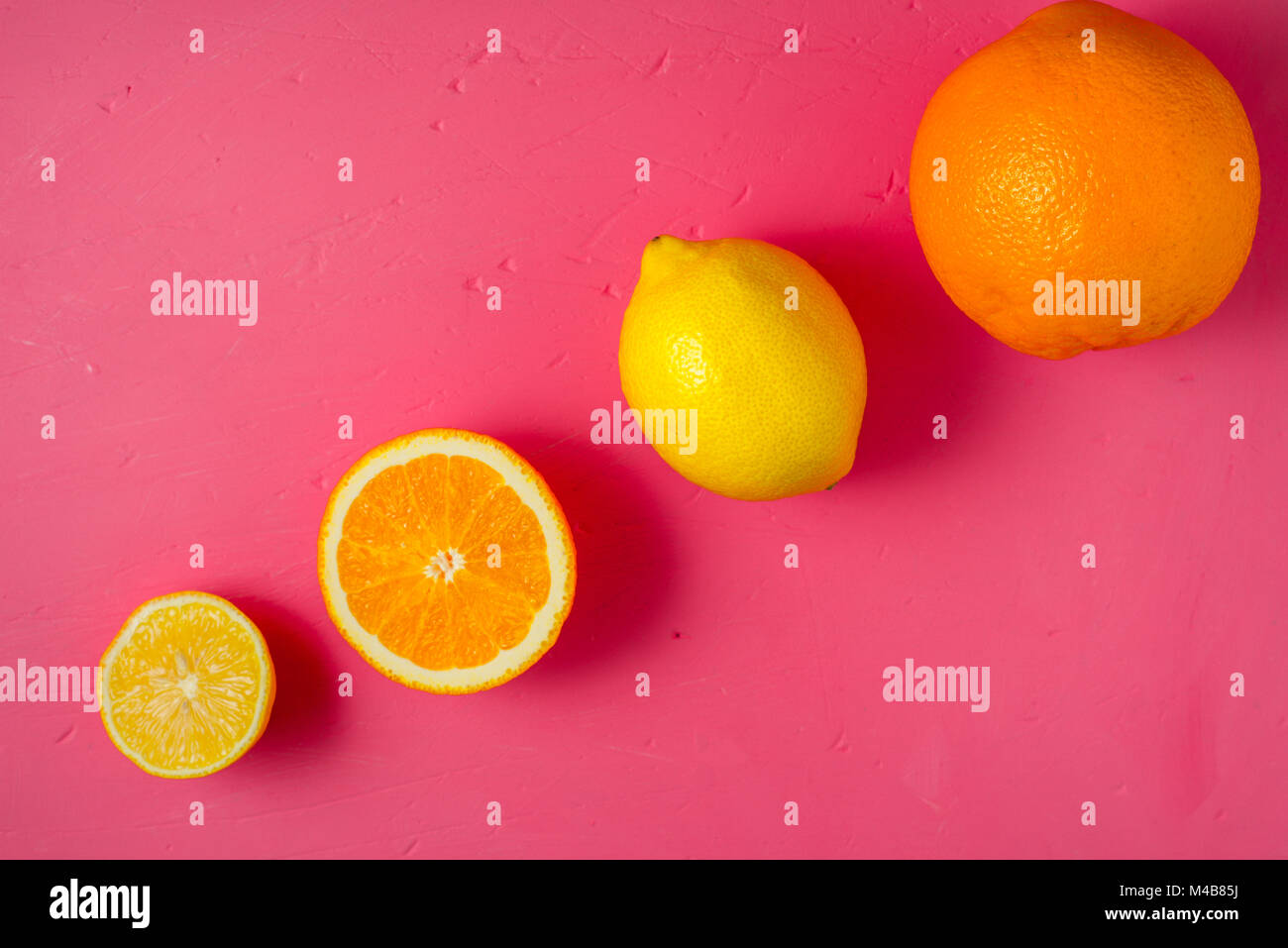 Lemons and oranges on the bright pink background top view - Stock Image