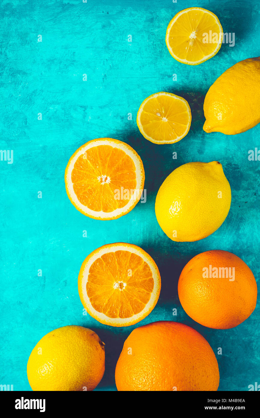 Lemons and oranges on the cyan background vertical - Stock Image