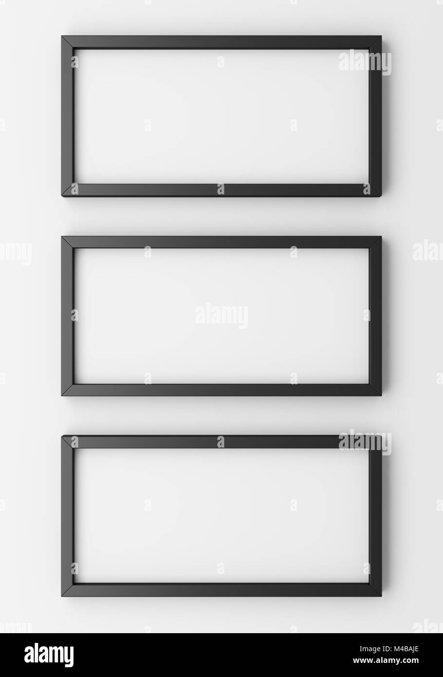 three blank black photo frames on white wall - Stock Image