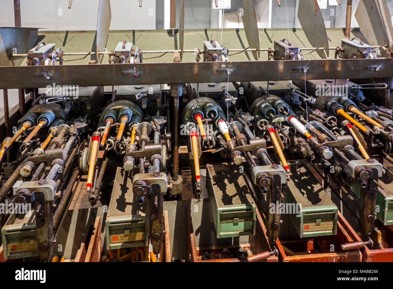Bobbins with yarns on spool machine in cotton mill / spinning-mill - Stock Image