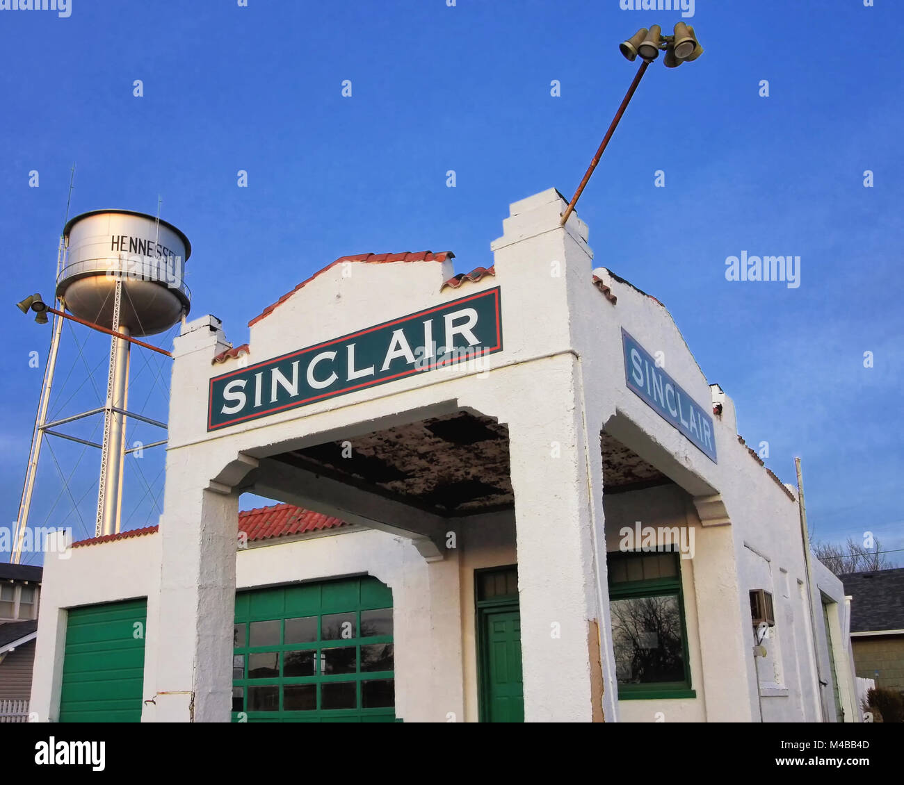 The Hennessy Oklahoma water tower stands behind the old Sinclair gas station on Highway 81. - Stock Image