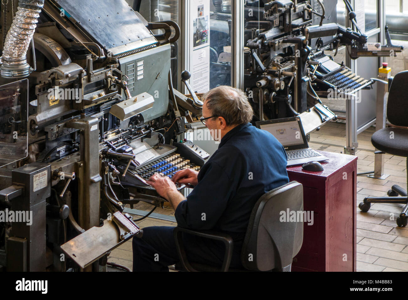 Linotype machine operator enters text on a 90-character keyboard at printing business - Stock Image
