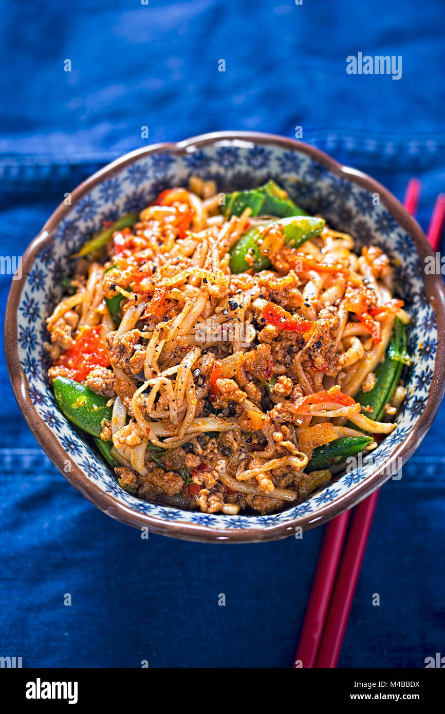 Sichuan spicy pork noodles with bean sprouts, sugar snap