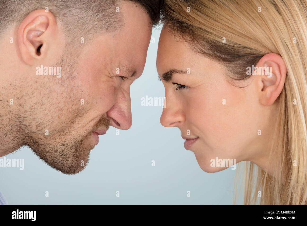 Close-up Of Young Couple Looking Angrily At Each Other - Stock Image