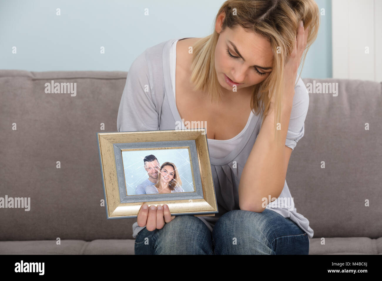 Sad Woman Holding Broken Picture Frame Of Couple In Love Stock Photo