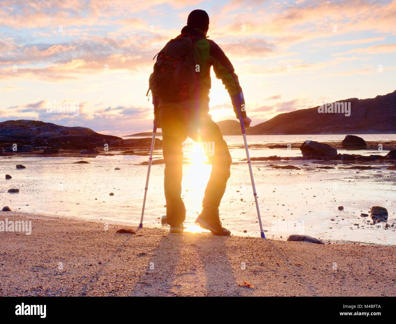 Happy disabled man on beach holding his forearm crutches above head, warm  sunset in background - Stock Image