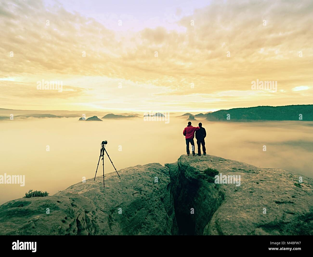 Two warm coat photographers with tripod shoot pictures of autumnal landscape below mountain.  Rainy misty day in Stock Photo