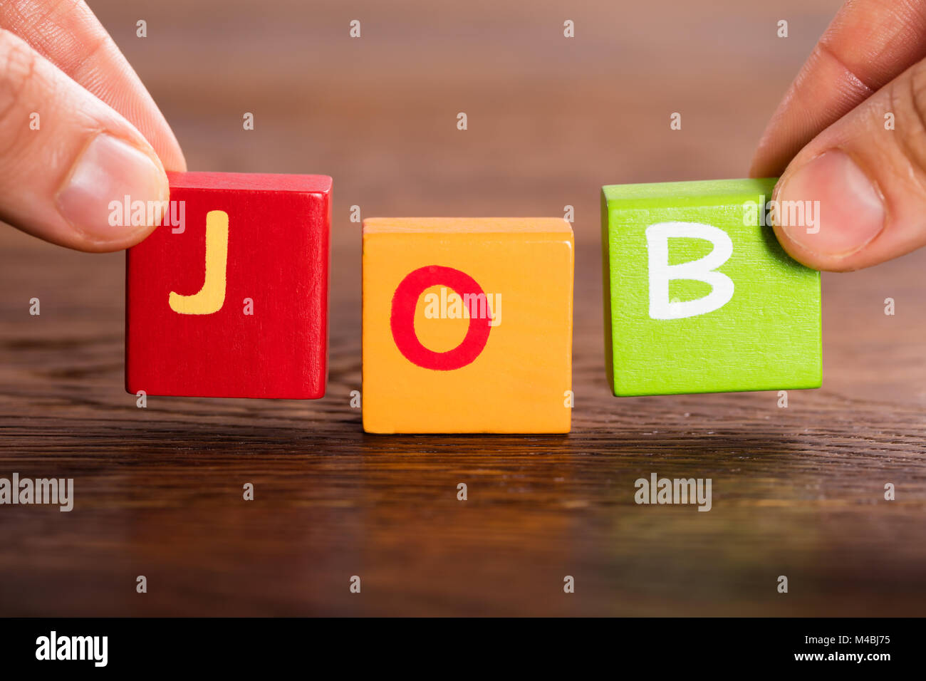 Person Hand Arranging Blocks For Making The Word Job On Table - Stock Image