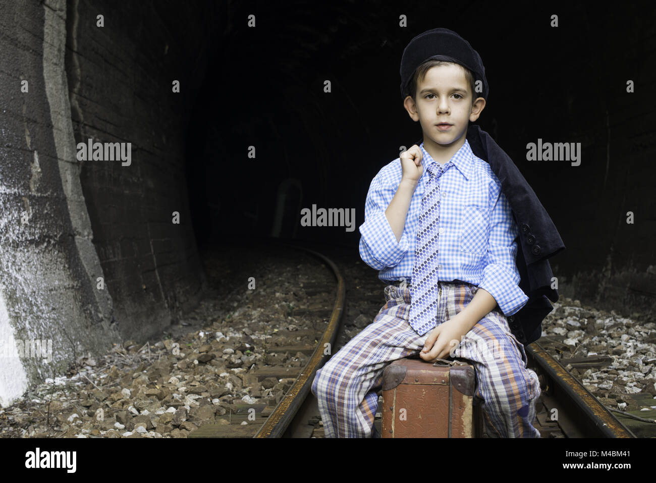 Child in vintage clothes sits on railway road Stock Photo
