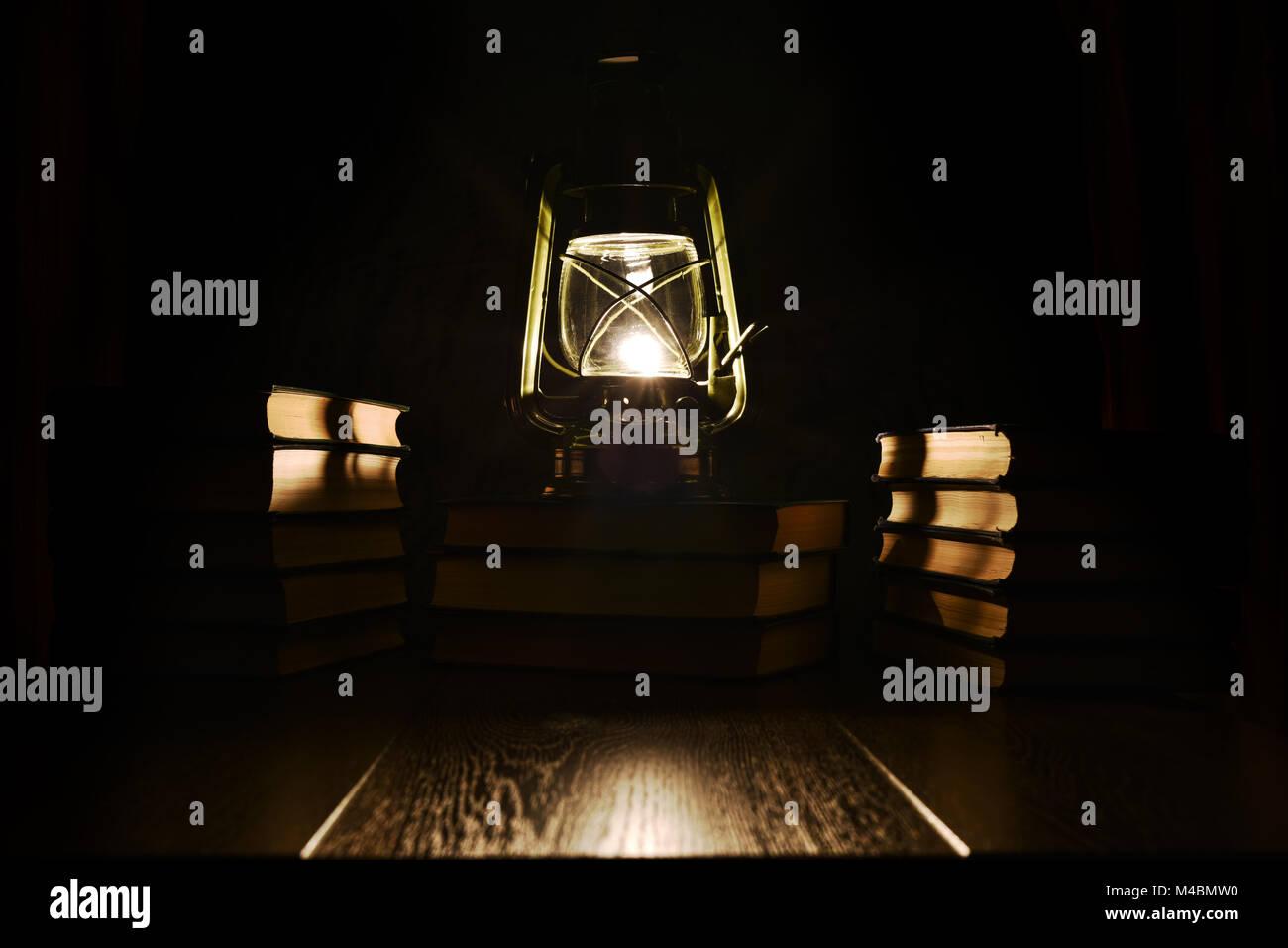 The light of kerosene lamp and books on the table - Stock Image