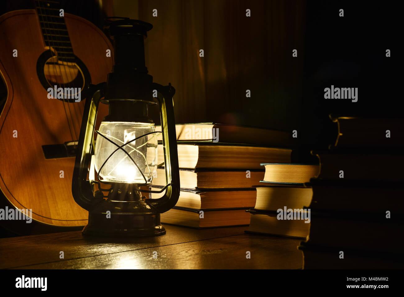 Luminous kerosene lamp, guitar and books on the table - Stock Image