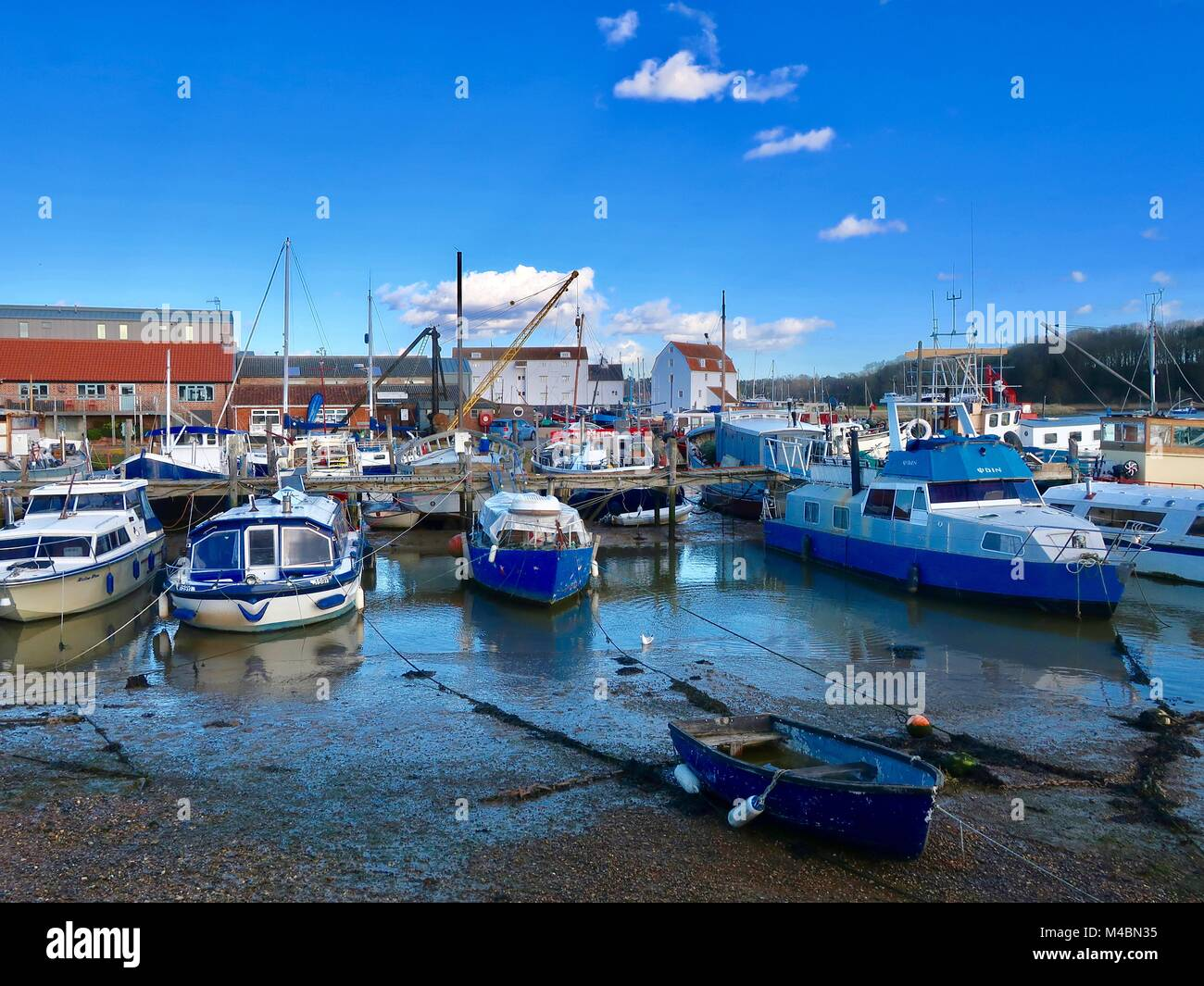 Boats moored in the mud at low tide. River Deben, Woodbridge, Suffolk. UK. Stock Photo