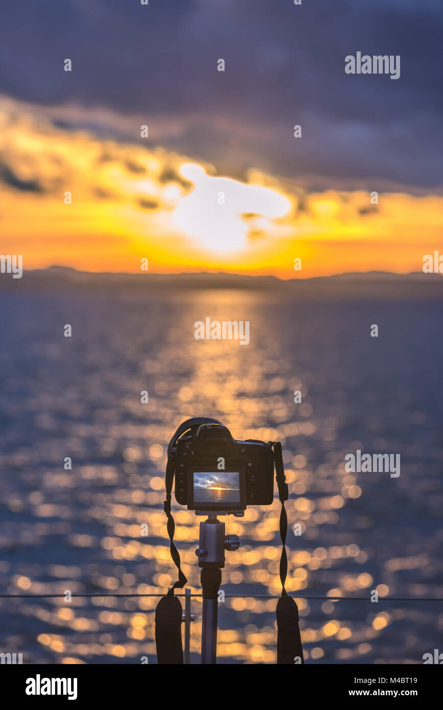 Camera on a tripod capturing the sunset - Stock Image