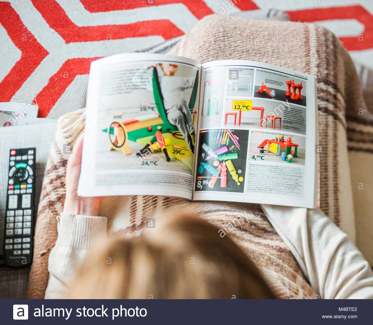 Woman reading IKEA catalog furnishing house kids furniture - Stock Image