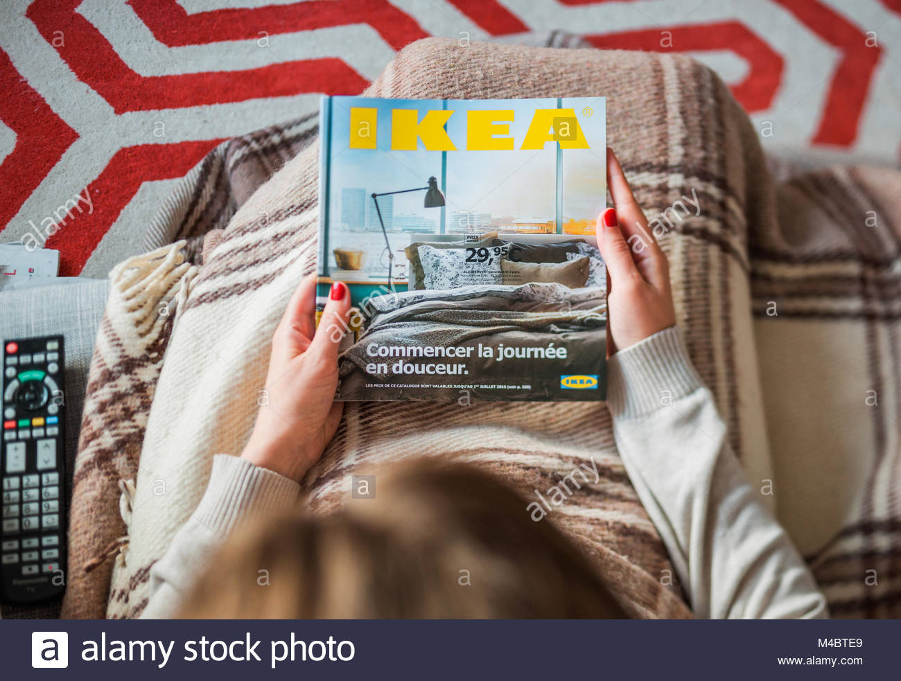 Woman reading IKEA catalog cover before furnishing house - Stock Image