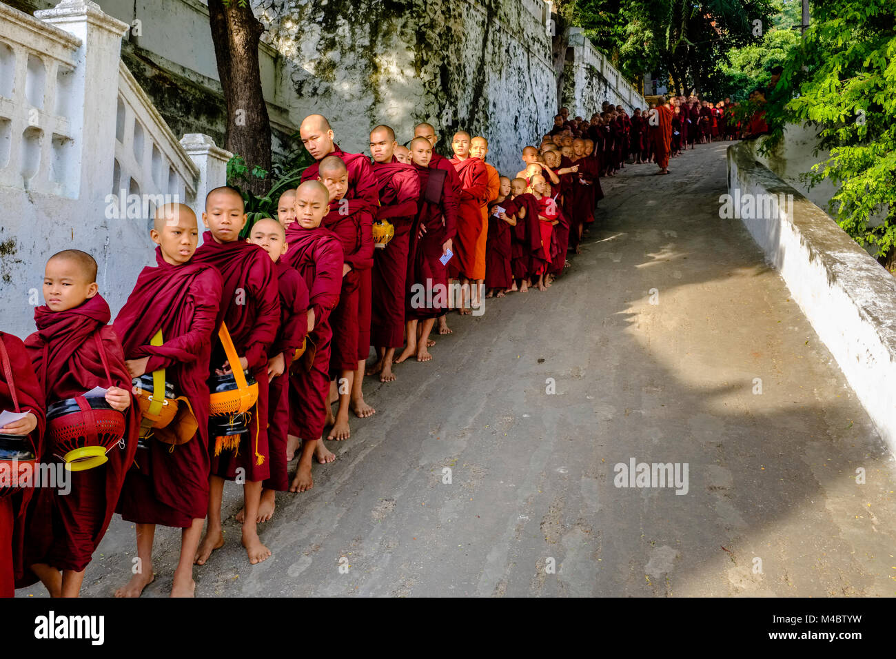 Buddhist monks are queuing in a long row to receive donations in a monastery - Stock Image