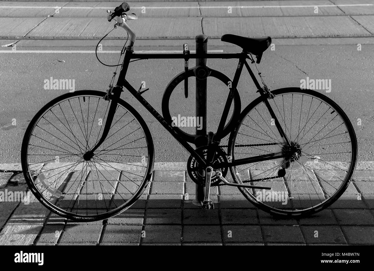 Bicycle in silhouette parked on the sidewalk of a street of Toronto, Canada - Stock Image