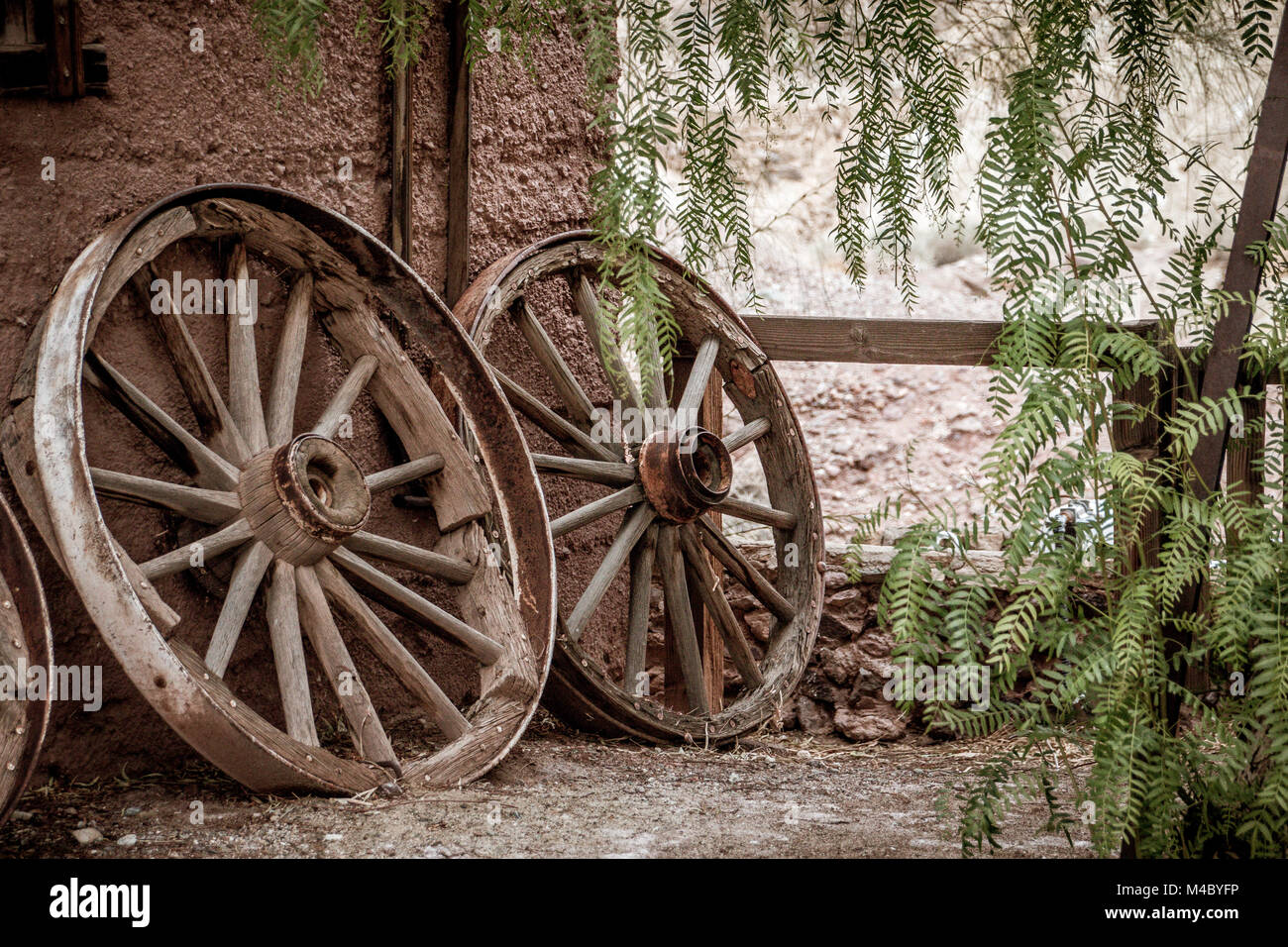 Old broken waggon wheels leaning against a wall - Stock Image