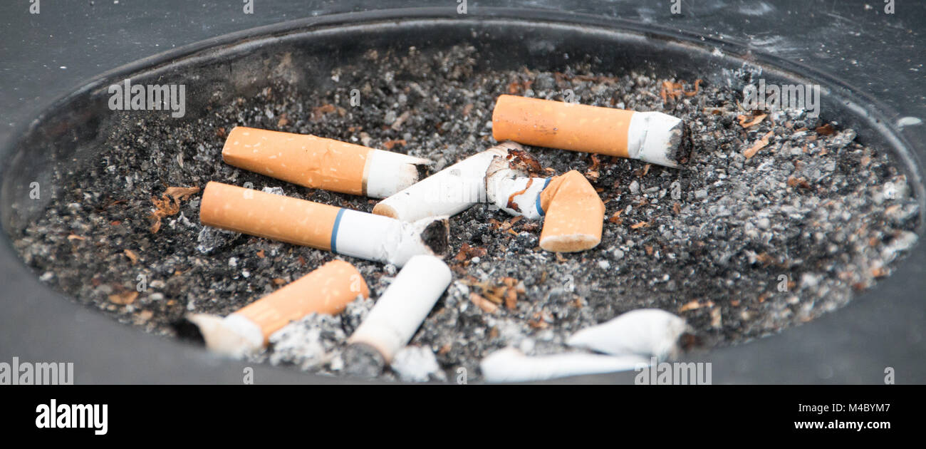 Dirty black ashtray with smoked cigarettes - Stock Image