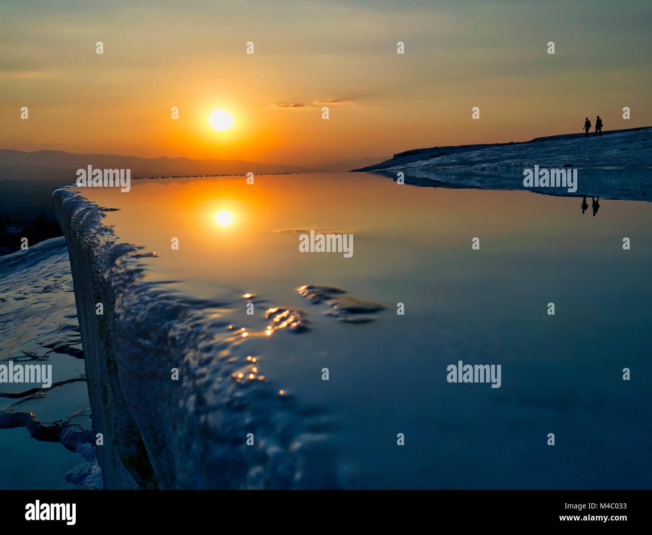 Silhouette of a couple walking at sunset among the geological phenomenon of the mineral rich thermal pools at Pamukkale, - Stock Image