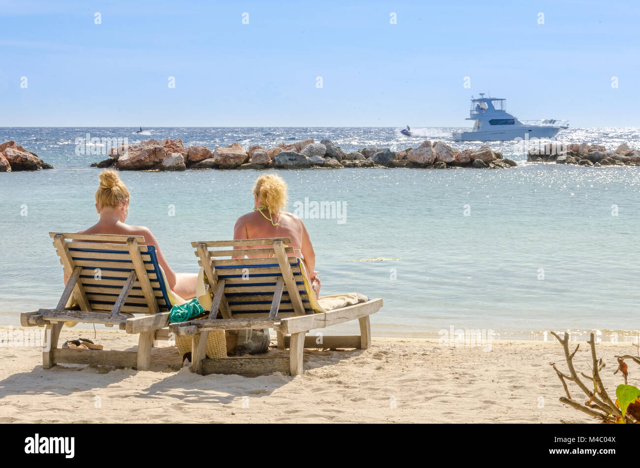 Two girls in a front row seats at the beach - Stock Image