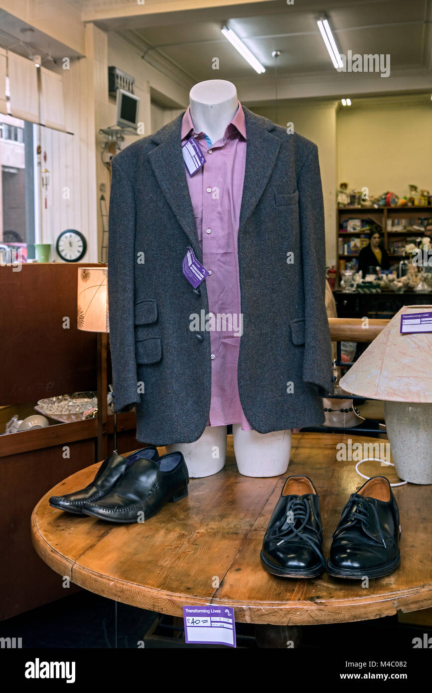 Secondhand clothes on display in a charity shop in Edinburgh, Scotland, UK. - Stock Image