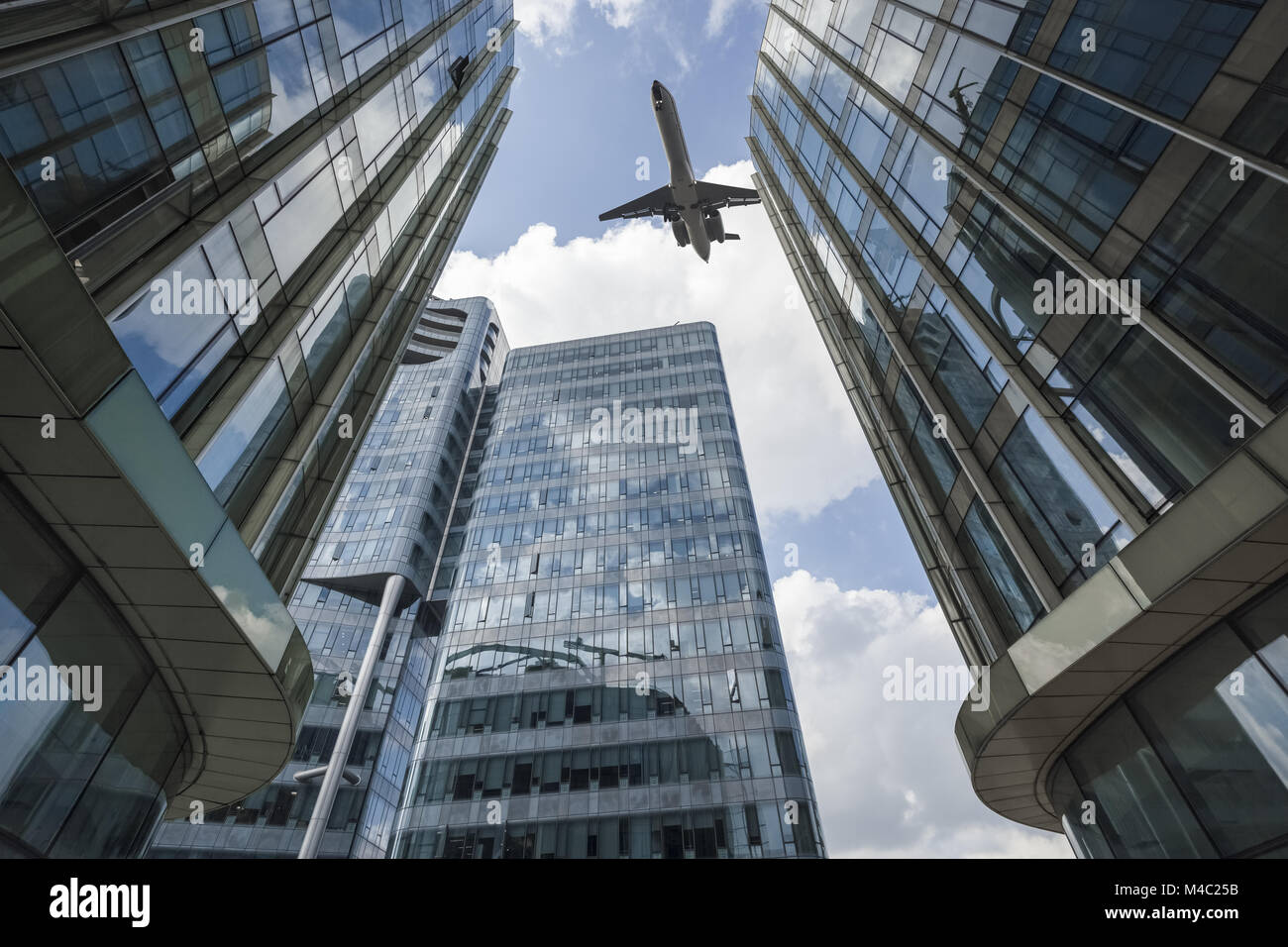 airliner flew above the modern glass building - Stock Image