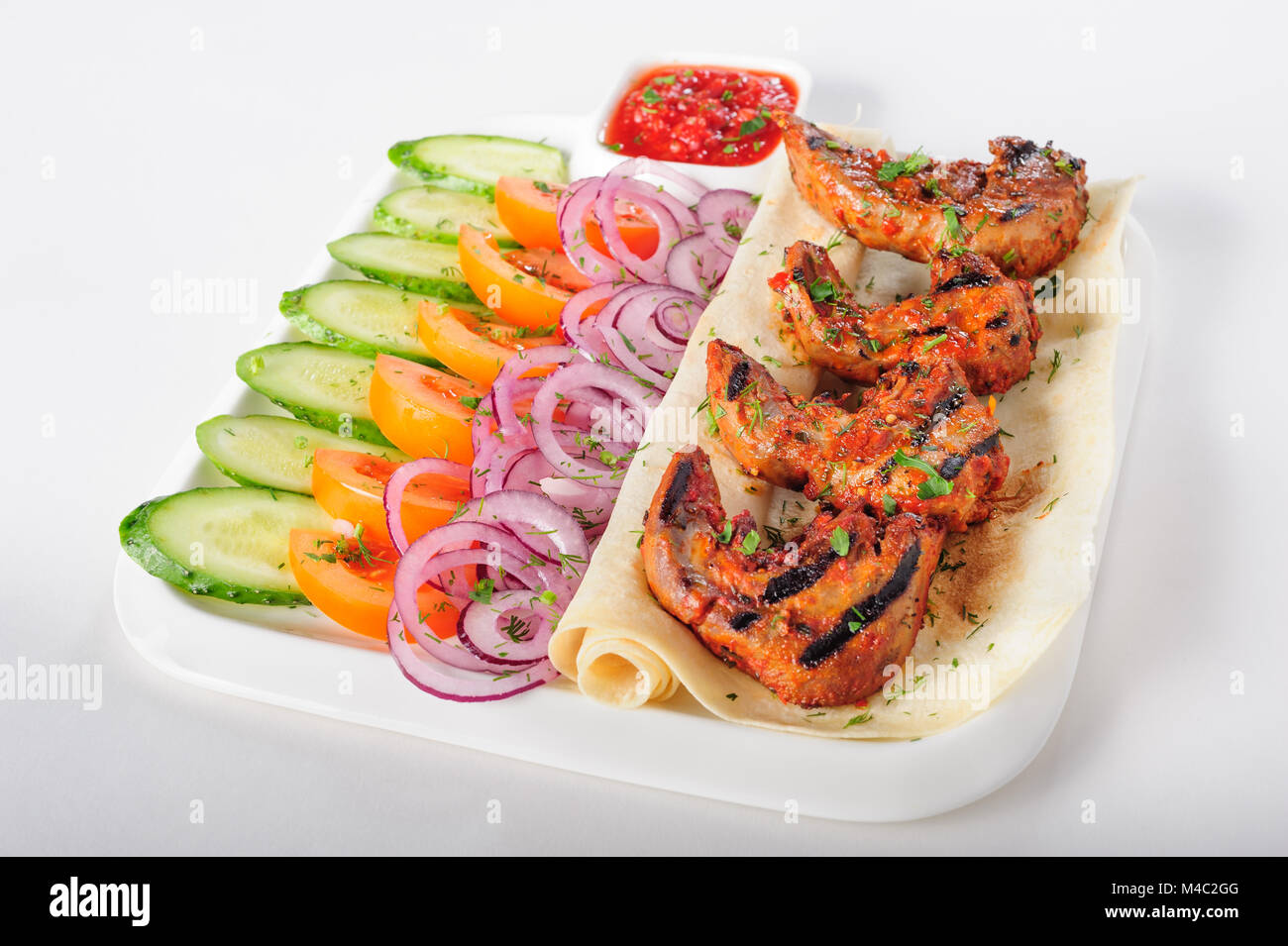 Grilled lamb tongues with fresh vegetables salad - Stock Image