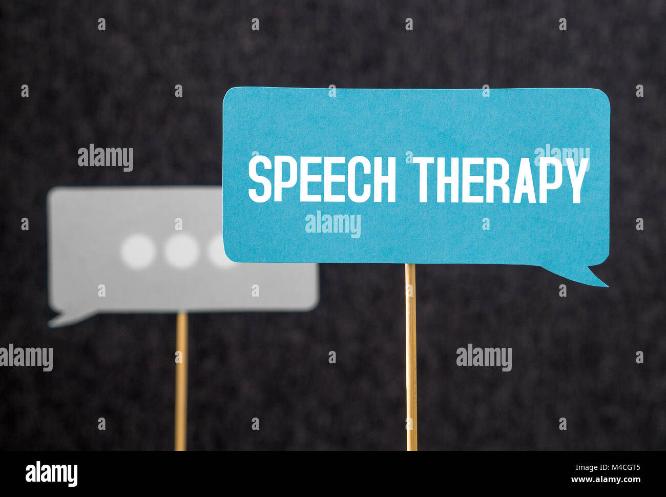 Speech therapy text on cardboard speech balloon or bubble on wooden stick. Stuttering, lisp and learning to talk - Stock Image
