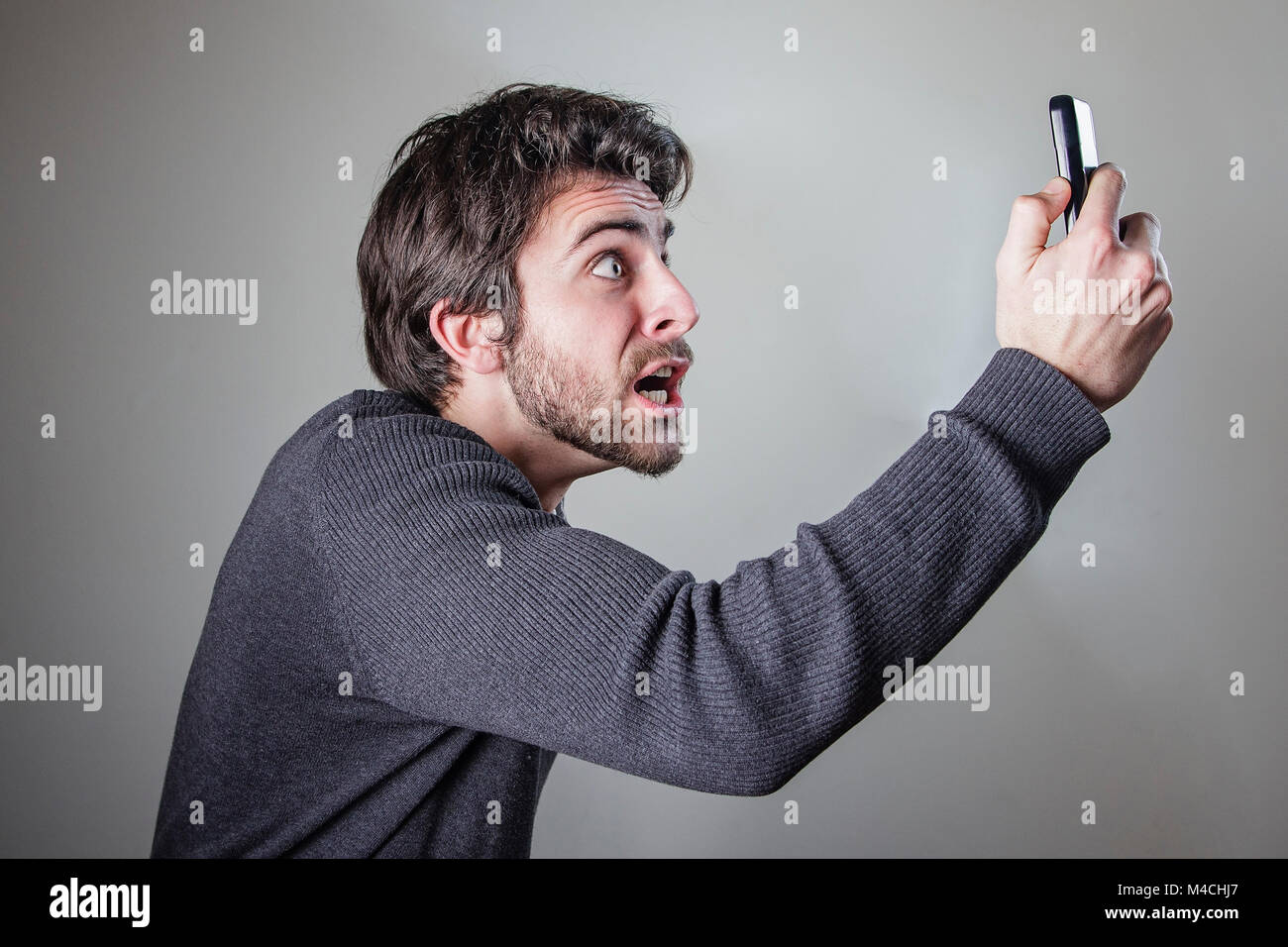 Outraged and angry man yelling at his phone - Stock Image