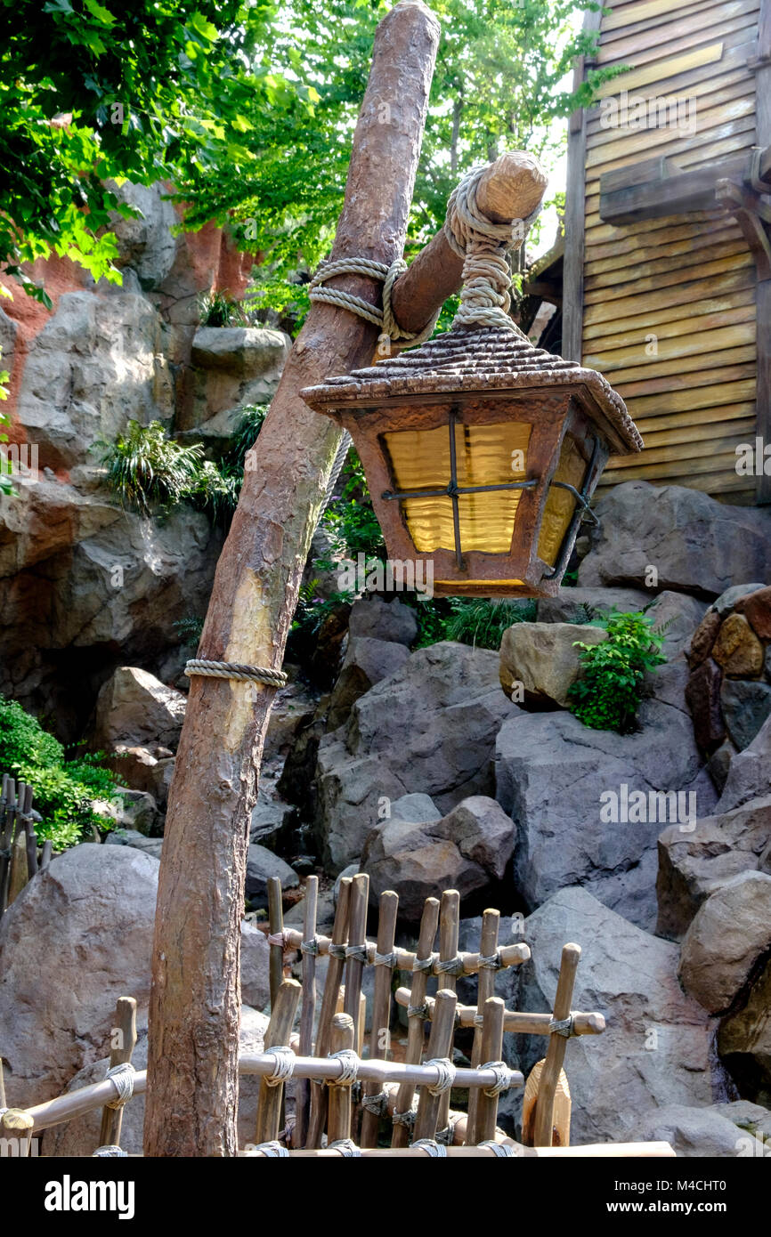 Rustic wooden lamp post tied with rope & old lamp hanging