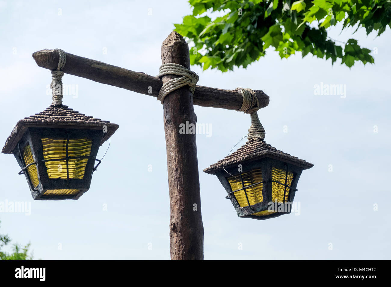 Close up of rustic wooden lamp post tied with rope two old lamps close up of rustic wooden lamp post tied with rope two old lamps with yellow glass hanging downees on top right disneyland tokyo aloadofball Images