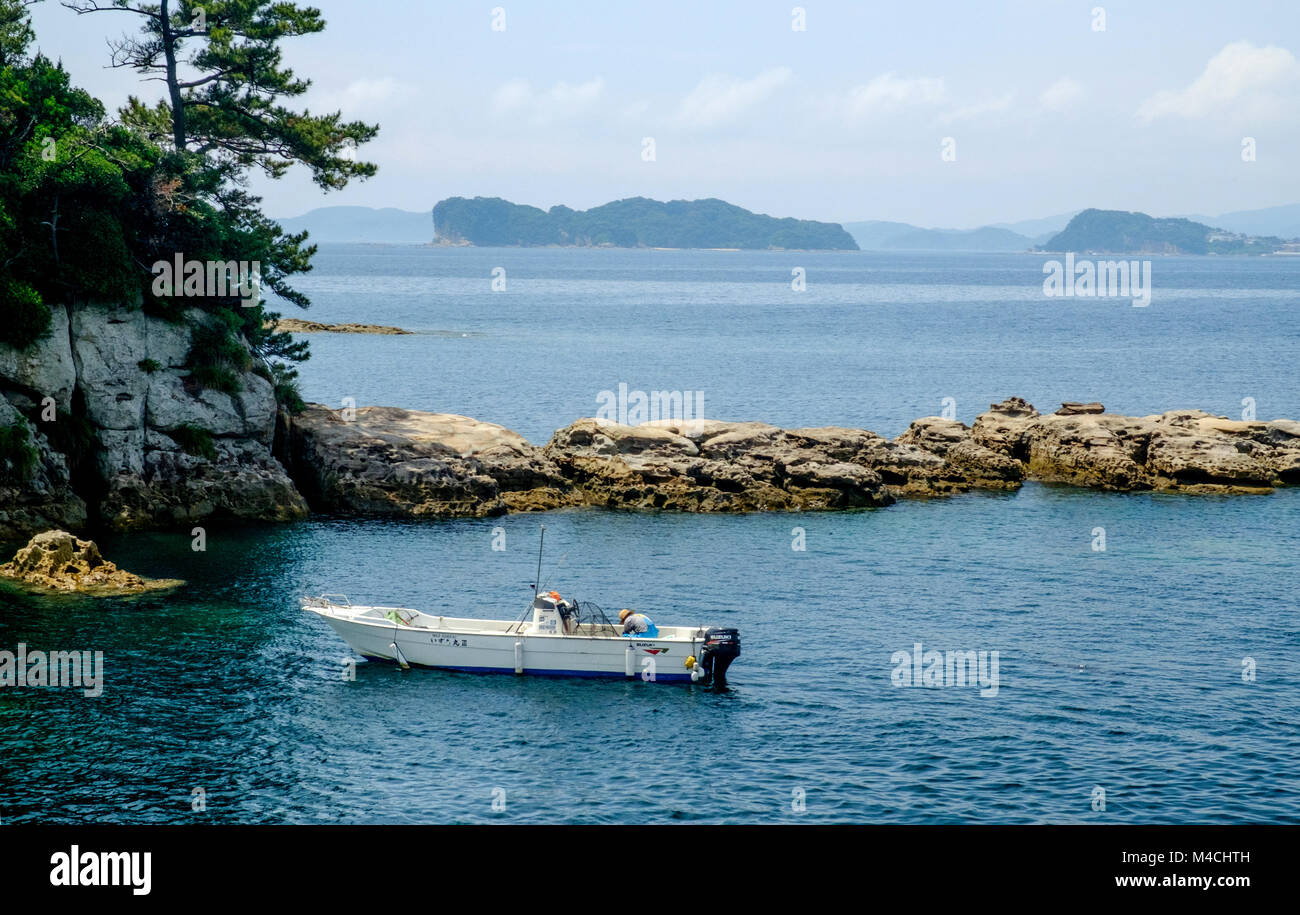 Fisherman bent down on his boat in the water. Rocks behind him. Rocks & trees to the left. Mountains & ocean - Stock Image