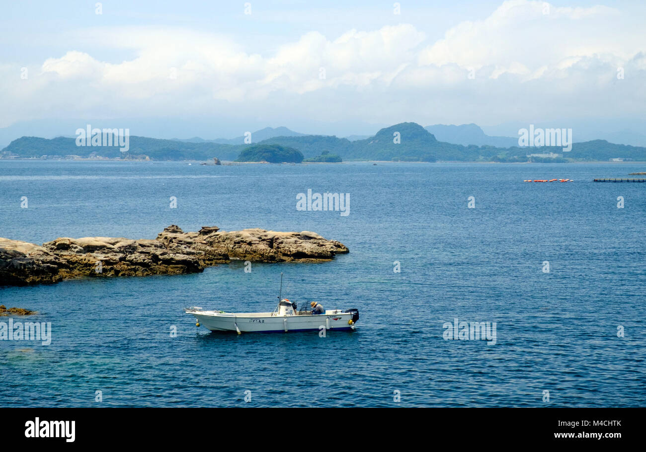 Fisherman bent down on his boat in the water. Rocks behind him. Mountains & ocean in the back. -99 Islands, - Stock Image