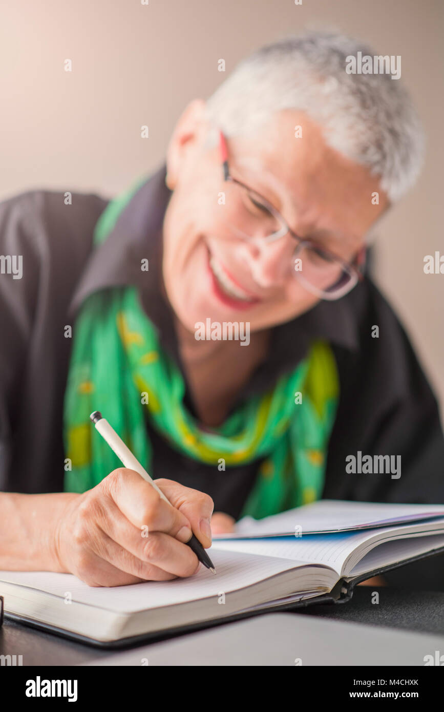 Writing an appointment in notebook - Stock Image