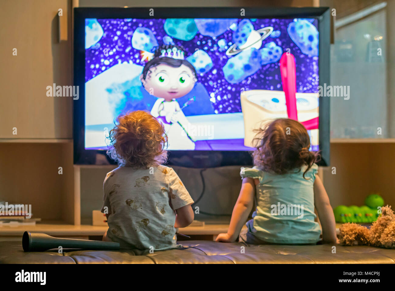Pre-school children watch cartoons on television. - Stock Image